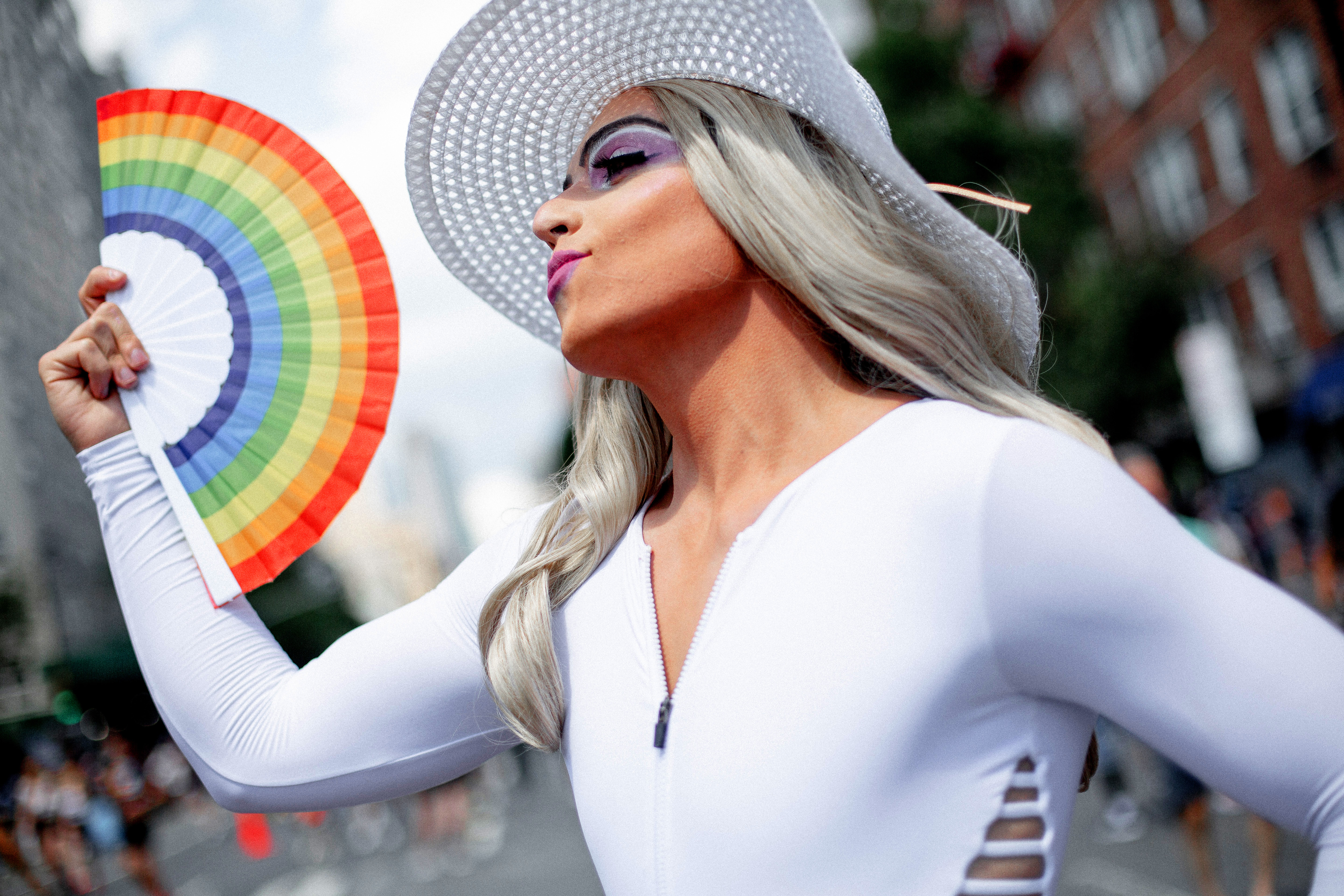 A closeup shot of a woman, wearing a white shirt and a white hat, waving a rainbow Pride fan.