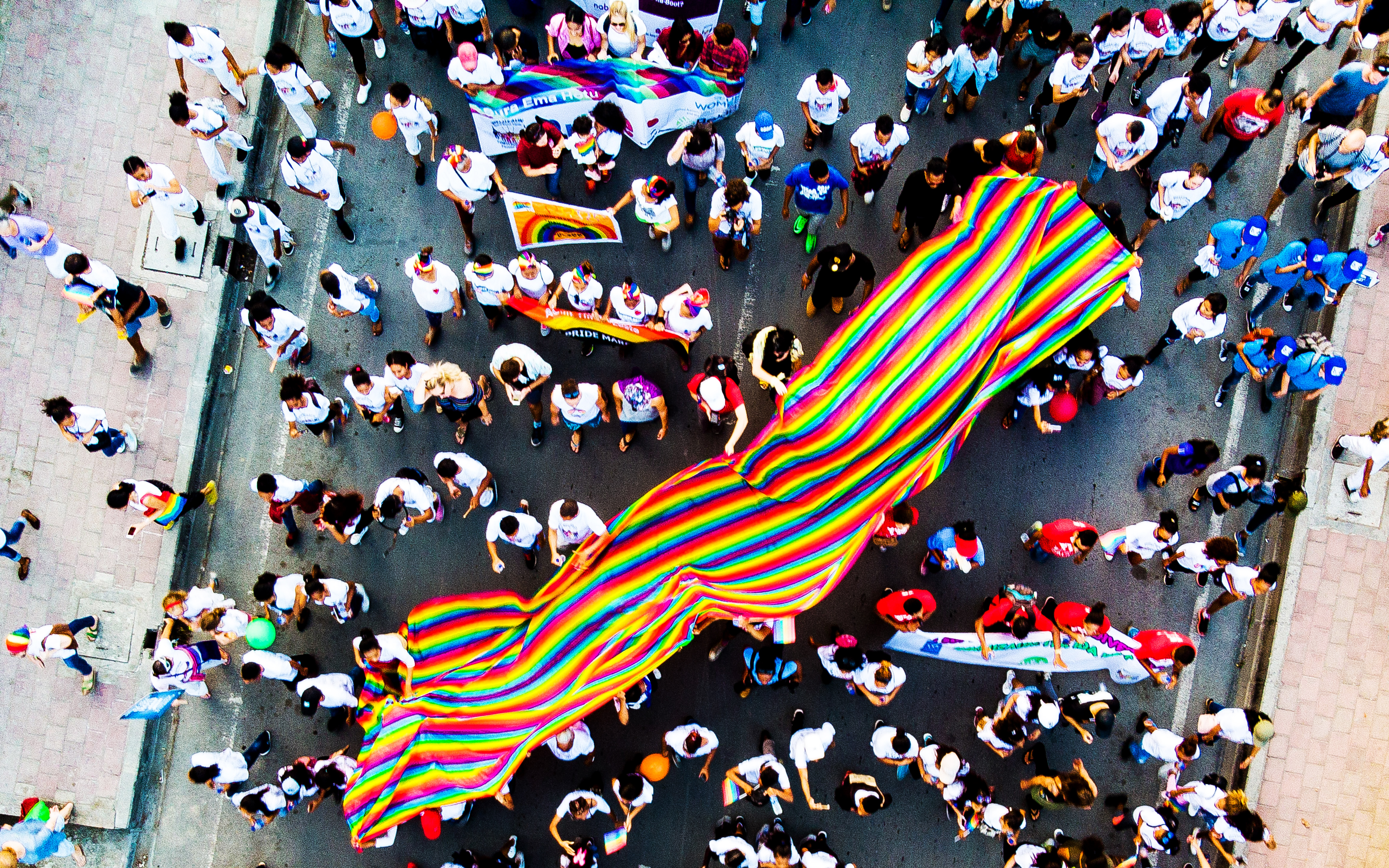 A crowd of Pride marchers holds up a rainbow Pride flag, shot from above.
