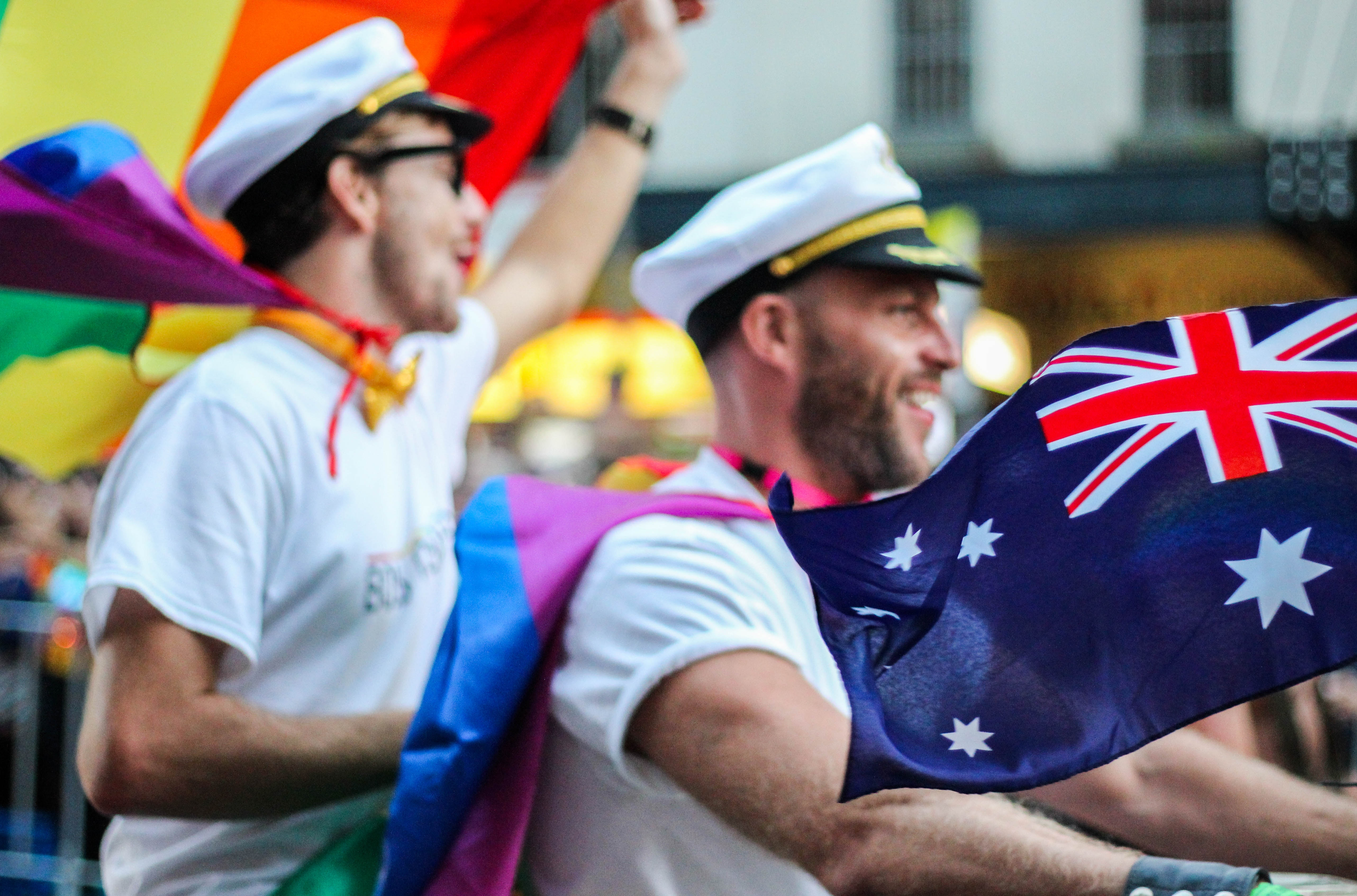A photo of two men marching in a parade. One is holding up an LGBTQ pride flag, and the other is holding the flag of Great Britain