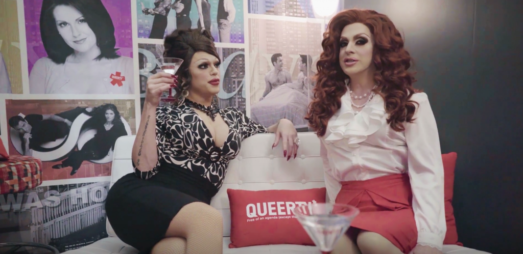 Morgan McMichaels and Pandora Boxx in the Queerty Will & Grace Social Lounge, where they are dressed like Karen and Grace from Will & Grace, and are holding martini glasses.