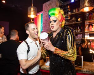 Local New York City Drag Queen Tina Burner poses with a guest at Queerty's Pride50 party. Tina has rainbow colored hair and is writing on a cup.