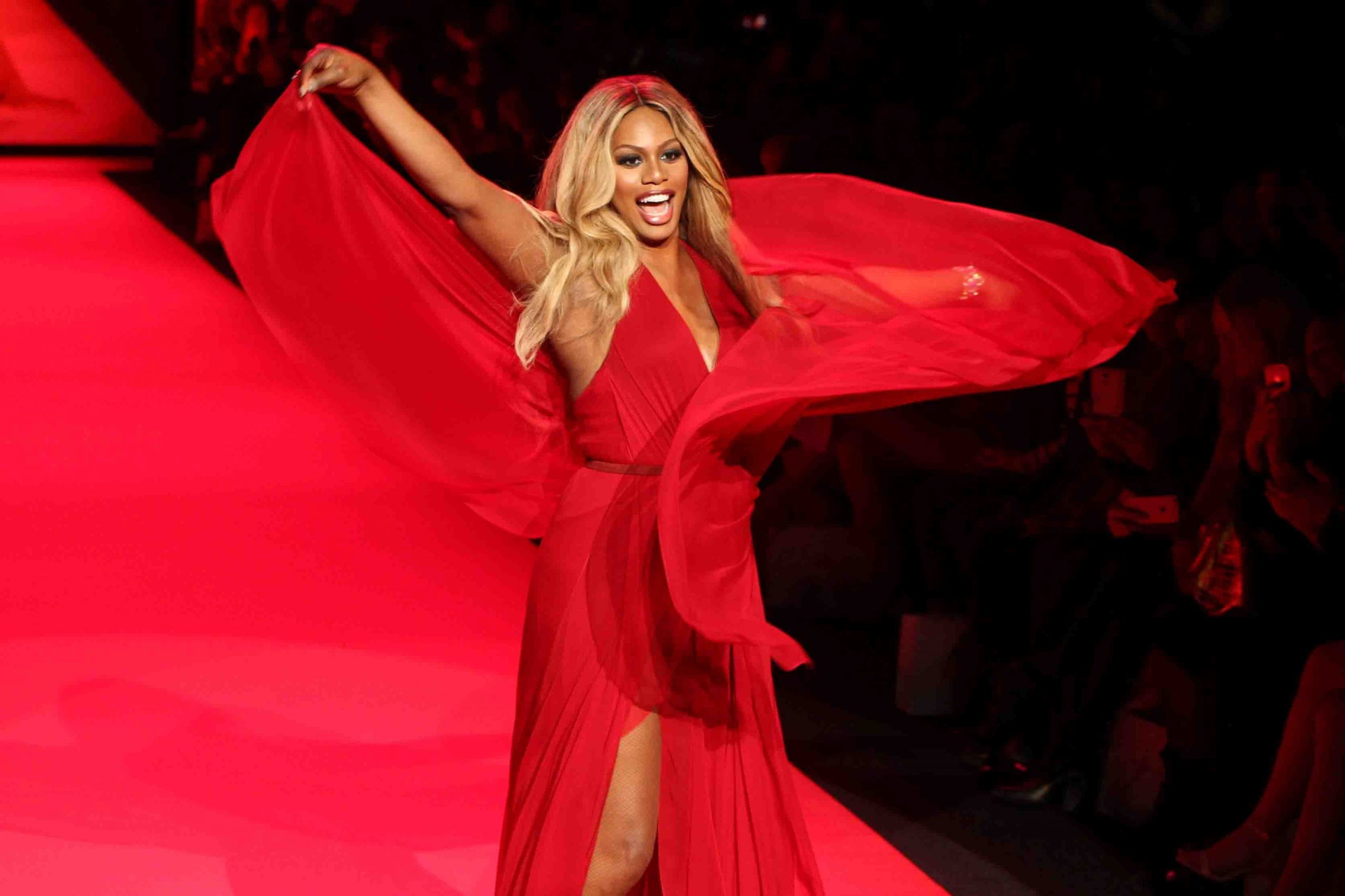 Trans actress Laverne Cox walks on the red carpet in a red gown that she is twirling in.
