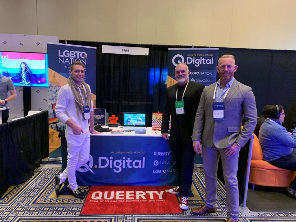 Q.Digital's Jordan Star, Joel Shoemaker and Scott Furman stand in front of a booth at the 2019 Out & Equal Conference.