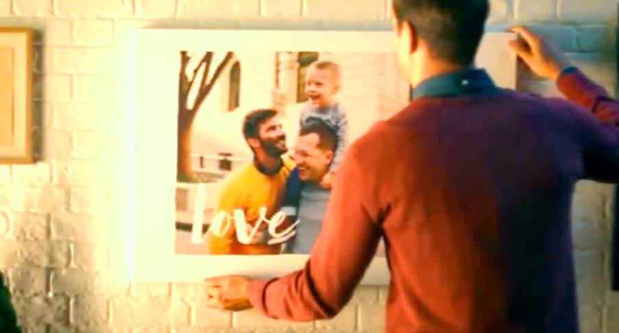 A still image from Shutterfly's holiday ad showing two gay dads and their son.