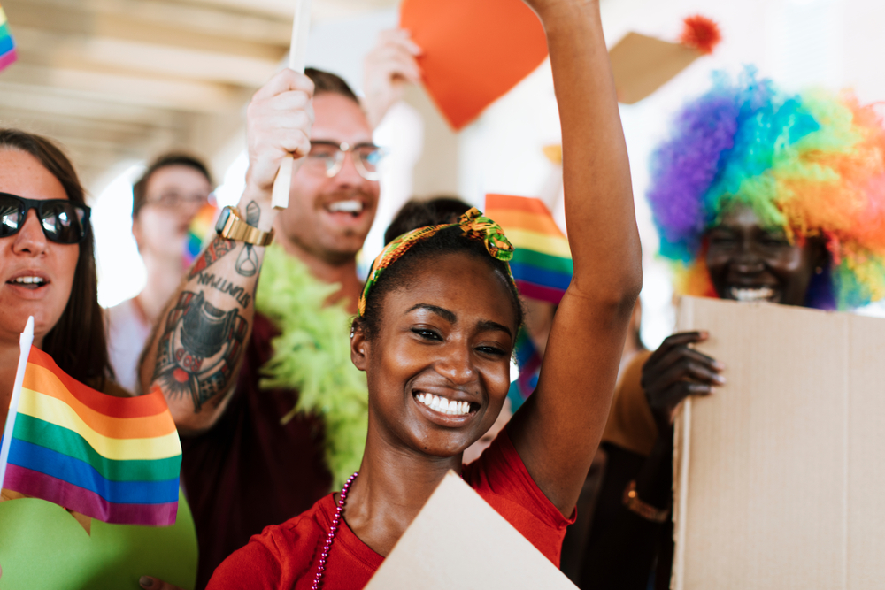A woman waving with rainbow LGBTQ flags all around her during a June gay pride parade.