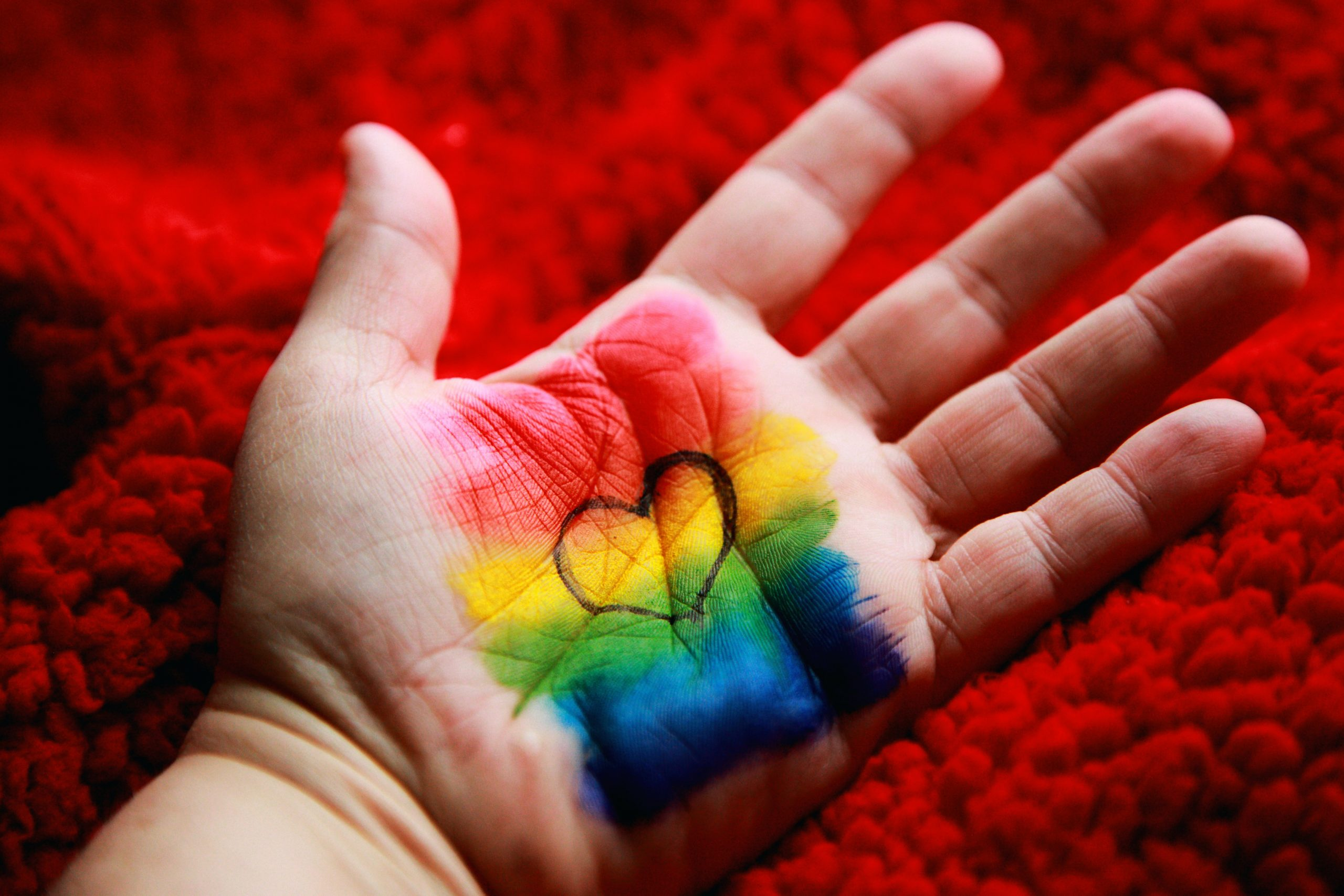 A close-up photo of a person's hand in front of a red carpet, with a rainbow and heart drawn on it.