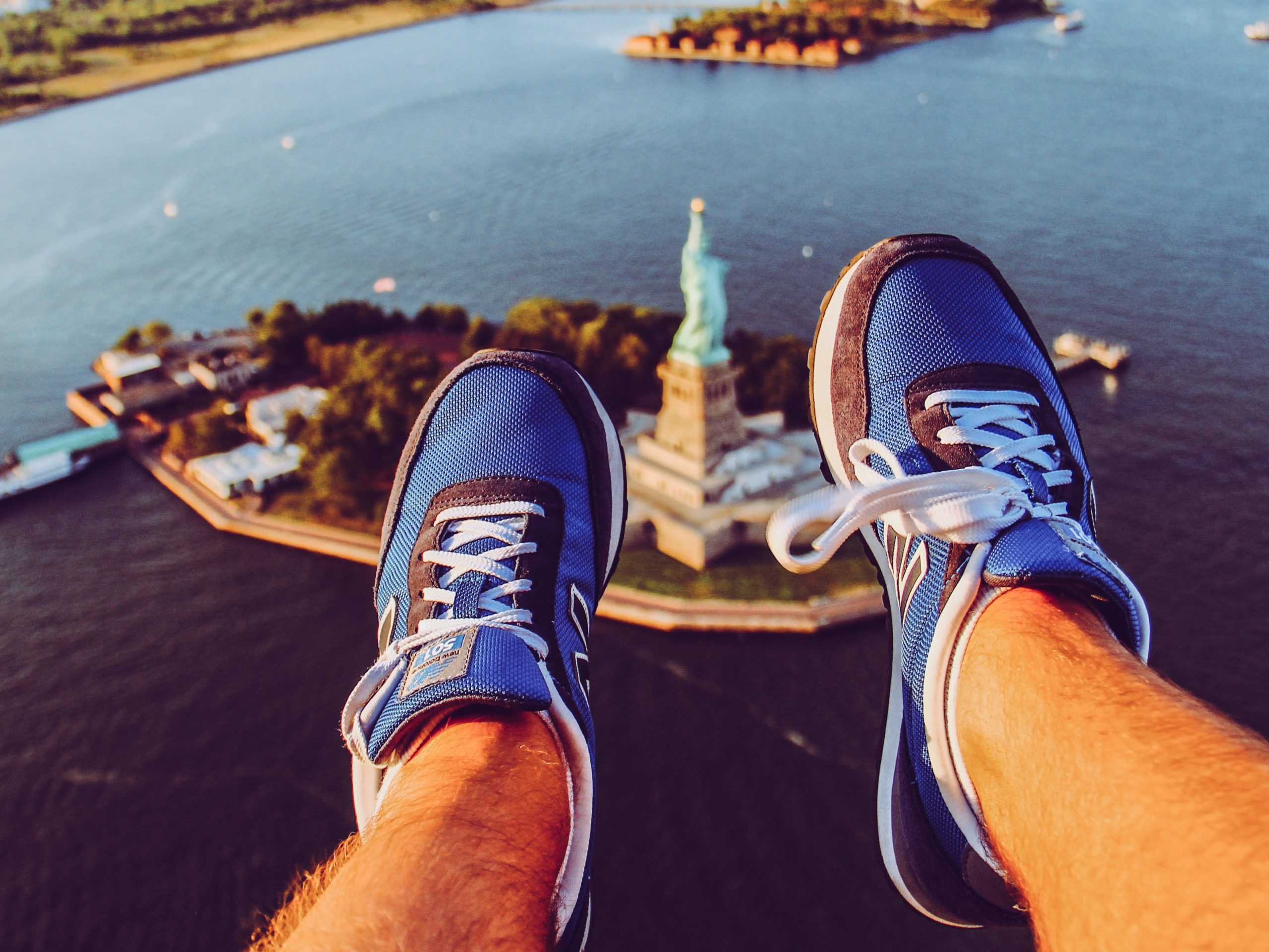 A sky eye view of NYC's Statue of Liberty, taken from the perspective of a man with the bottom of his legs in the foreground.