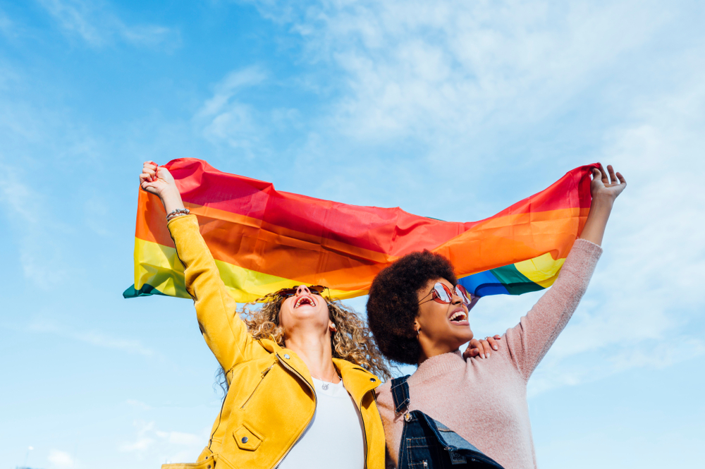 Two women hugging and holding a rainbow LGBTQ pride flag against a blue sky.