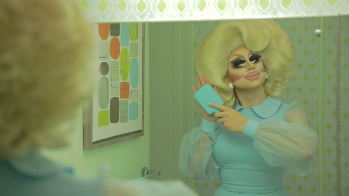 RuPaul's Drag Race star Trixie Mattel combs her hair for a video shoot in a vintage bathroom