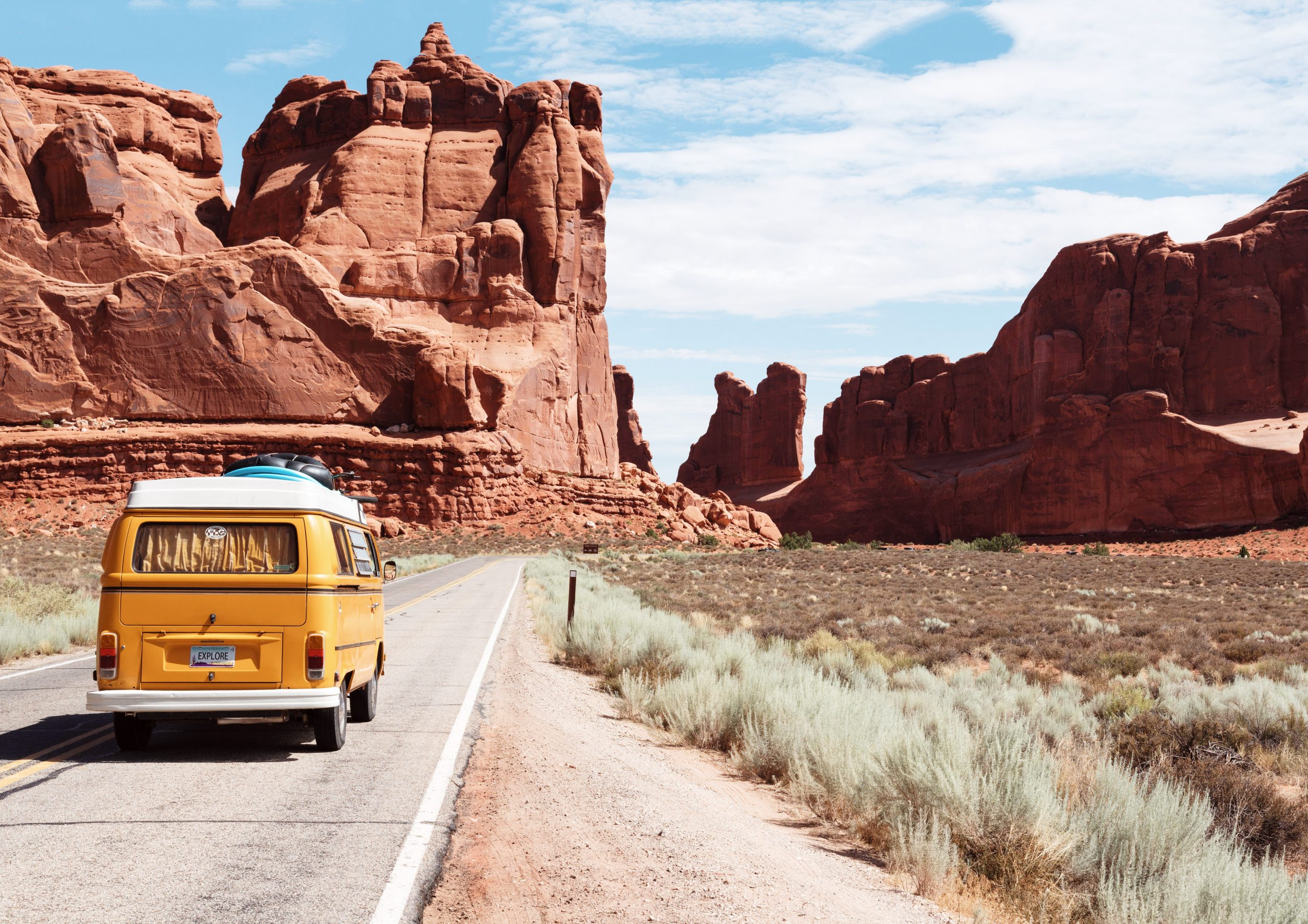 A yellow camper van on a highway drives toward the grand canyon, in a retro vibe photo.