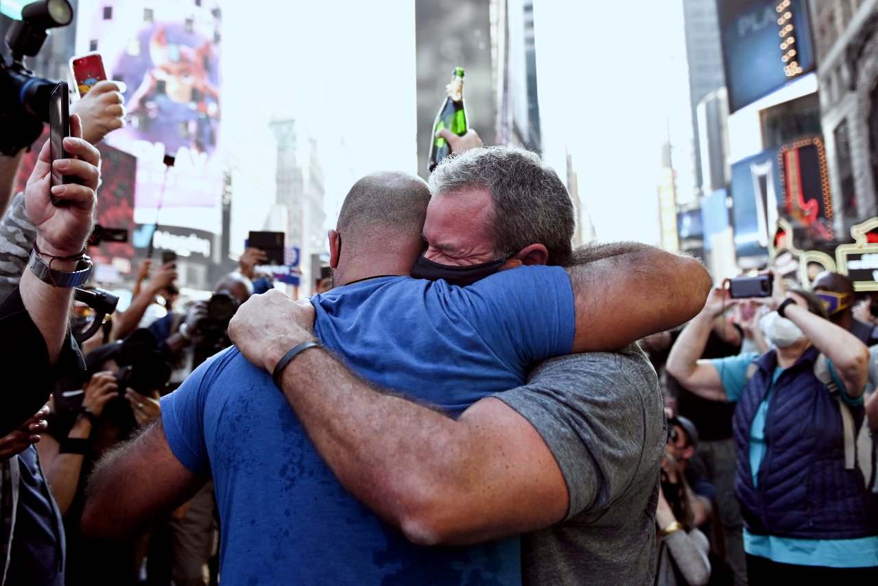 Two gay men hugging in Times Square on election night in New York City, when Joe Biden was announced as President.